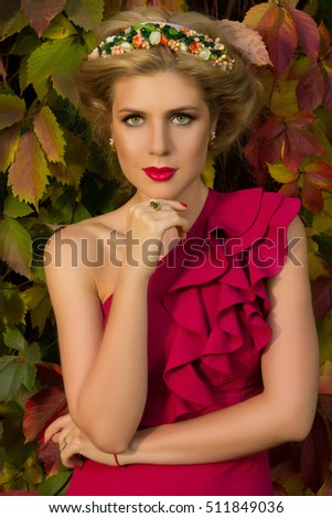 beautiful girl in red dress posing on a background of autumn leaves
