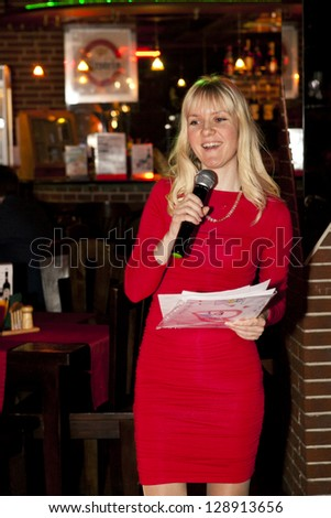beautiful girl in red dress with mic as a party chief