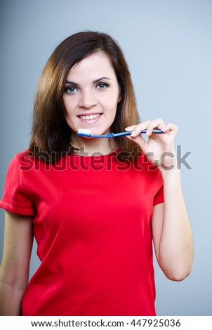 beautiful girl in red shirt holding toothbrush in the mouth, on a gray background - stock photo