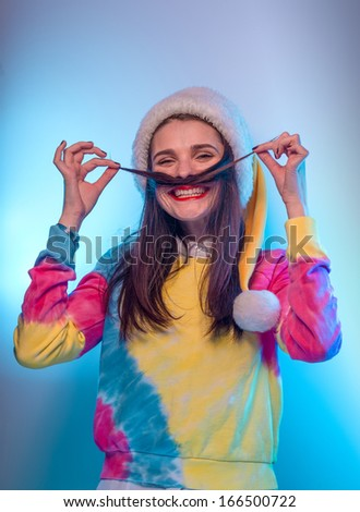 Beautiful girl in Santa Claus hat. Making mustache from her hair