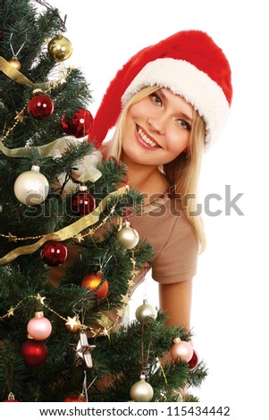 Beautiful girl in santa hat near christmas tree,decorated background - stock photo