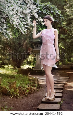 Beautiful girl in silk pink dress, near blossom tree, smelling flowers... - stock photo