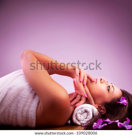 Beautiful girl in spa salon, pretty woman relaxing on massage table, attractive young female isolated on pink background, healthy lifestyle, beauty care, treatment and therapy concept - stock photo