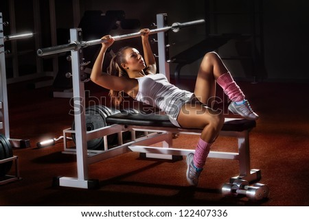 Beautiful girl in sports to a hall carries out exercise with a bar in the gym Bar Bench Press - stock photo