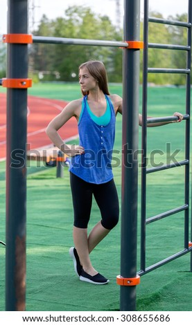 beautiful girl in sportswear on the playground in the park, outdoor - stock photo