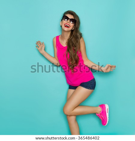 Beautiful girl in sunglasses, jeans shorts and pink top dancing with arms outstretched. Three quarter length studio shot on teal background. - stock photo