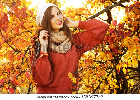 Beautiful girl in the autumn forest in knitted things