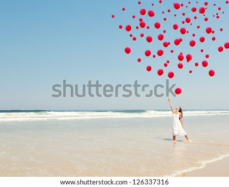 Beautiful girl in the beach dropping red ballons in the sky - stock photo