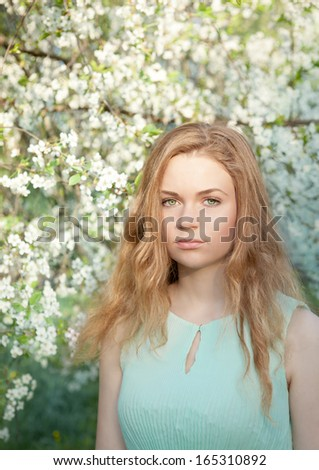 Beautiful girl in the blooming garden