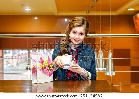 Beautiful girl in the cafe opens a white gift box - stock photo