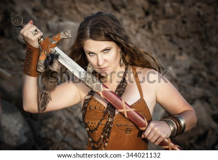 Beautiful girl in the clothes of a Viking or Amazon, with a sword on a background of stones. - stock photo