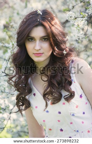 beautiful girl in the flowers of the tree - stock photo