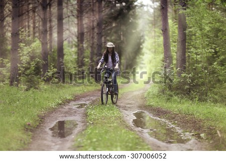 Beautiful girl in the forest landscape with sun rays