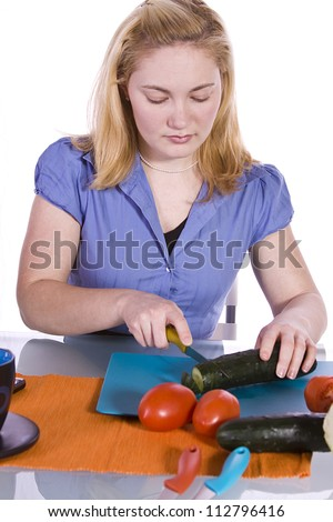 Beautiful Girl  in the Kitchen Cutting Tomatoes and Cucumber while haveing Wine - stock photo