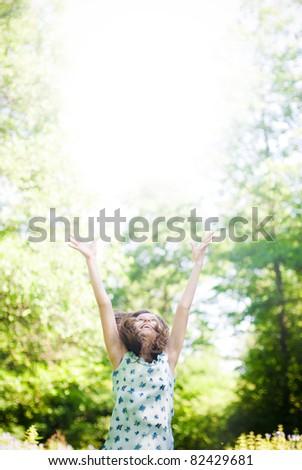 beautiful girl in the meadow jumping the sun - stock photo