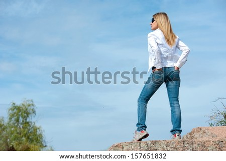 Beautiful girl in the open air, on a rock against the sky