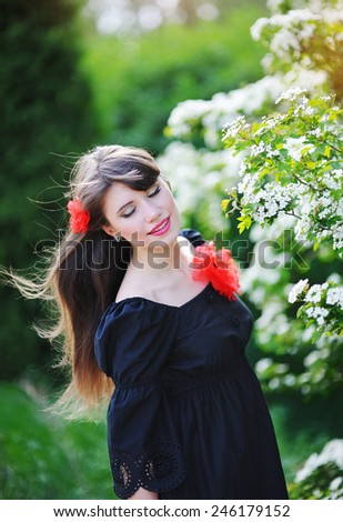 beautiful girl in the park in spring with a red flower in her hair. - stock photo