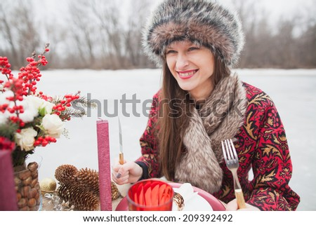 beautiful girl in the park in winter, in a fur cap on a romantic dinner - stock photo