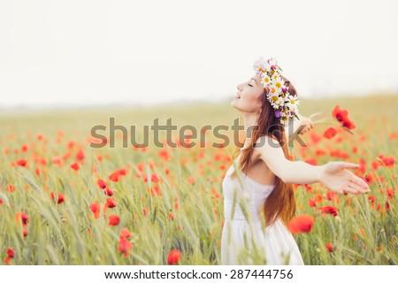 beautiful girl in the poppy field - stock photo