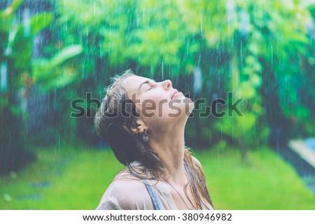 beautiful girl in the rain . Wet hair and shirt . Tropical rain  - stock photo