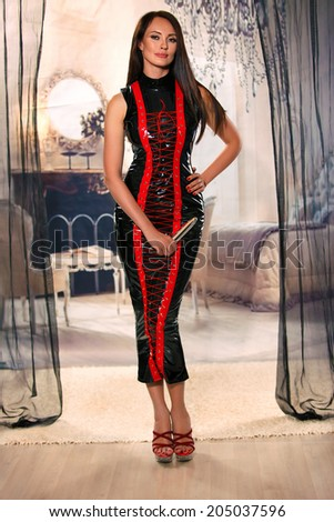 Beautiful girl in the sexy latex long dress - stock photo
