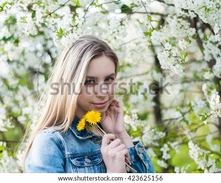 Beautiful girl in the  spring cherry blossoming garden - stock photo