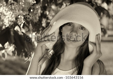 beautiful girl in the white hat beside a flowering tree - stock photo