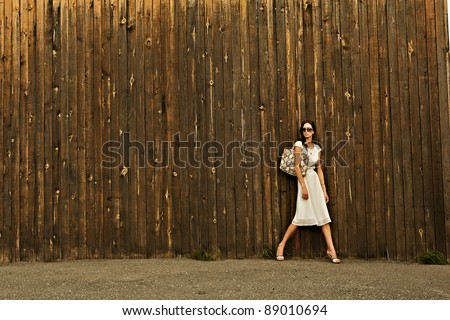 beautiful girl in white dress and bag against the wall with a wooden texture