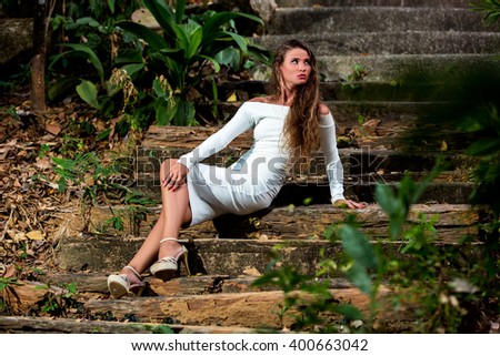 Beautiful girl  in white dress sitting on stairs in the tropical park