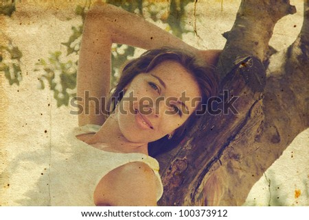 Beautiful girl in white dress sitting on the tree. Photo in old image style. - stock photo