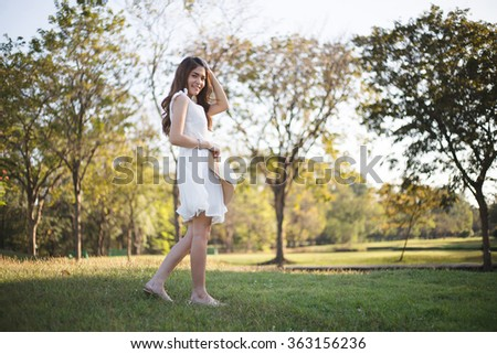 Beautiful girl in white dress walking on the grass field in the park - stock photo