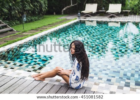 Beautiful girl in white tunic enjoying at the edge of the luxury pool - stock photo