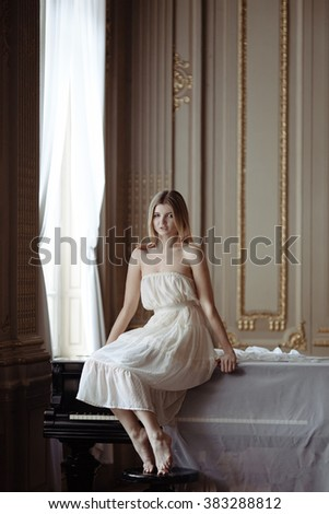 Beautiful girl in white vintage dress and a piano in rich interior.