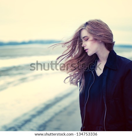 beautiful girl in windy conditions on the road in a field - stock photo