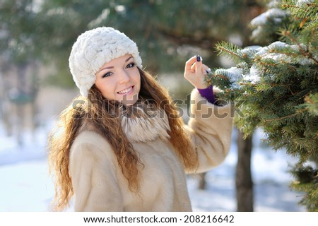 beautiful girl in winter hat walks - stock photo