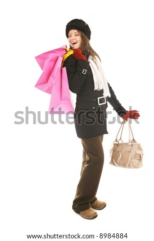 beautiful girl in winter outfit carrying gift bags after a sale; isolated on white - stock photo
