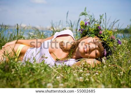 beautiful girl in  wreath of flowers sleep in  meadow on sunny day - stock photo