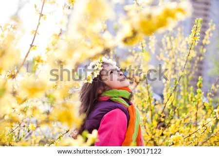 Beautiful girl in yellow flowers looking  up