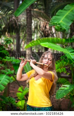 Beautiful girl in yellow shirt playing Indian traditional bamboo flute in banana and palm tree forest Varkala, Kerala, India - stock photo