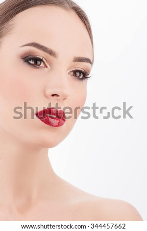 Beautiful girl is caring of her skin. She has red lipstick on her lips and naked shoulders. The lady is looking forward with desire. Isolated - stock photo