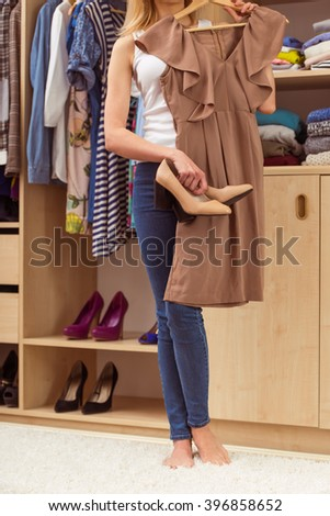 Beautiful girl is choosing a dress and shoes in her dressing room, cropped