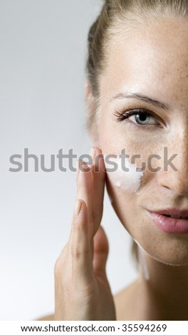 Beautiful girl is creaming her face. - stock photo