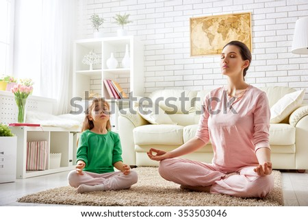 beautiful girl is engaged in yoga with her daughter - stock photo