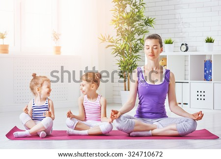 beautiful girl is engaged in yoga with her daughters - stock photo