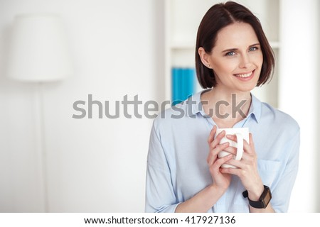 Beautiful girl is enjoying hot drink - stock photo
