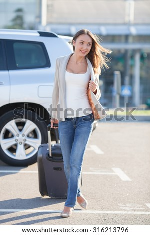 Beautiful girl is going with her suitcase to the airport from her car. She is ready for her journey. The lady is looking aside and smiling - stock photo