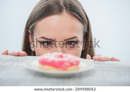 Beautiful girl is looking at unhealthy donut with appetite. It is situated on a table. Isolated on a white background - stock photo