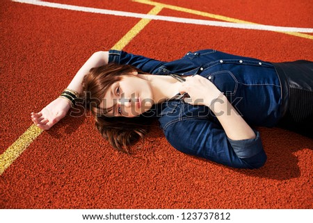 Beautiful girl is lying on playground and looking at the camera. - stock photo