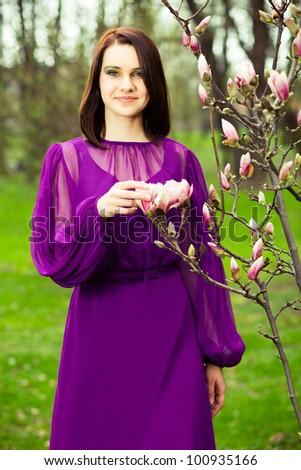 Beautiful girl is posing next to magnolias tree. - stock photo