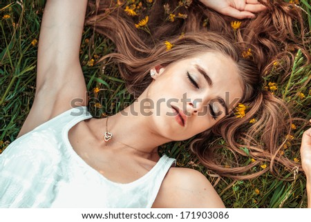 Beautiful girl is relaxing lying on the grass - stock photo